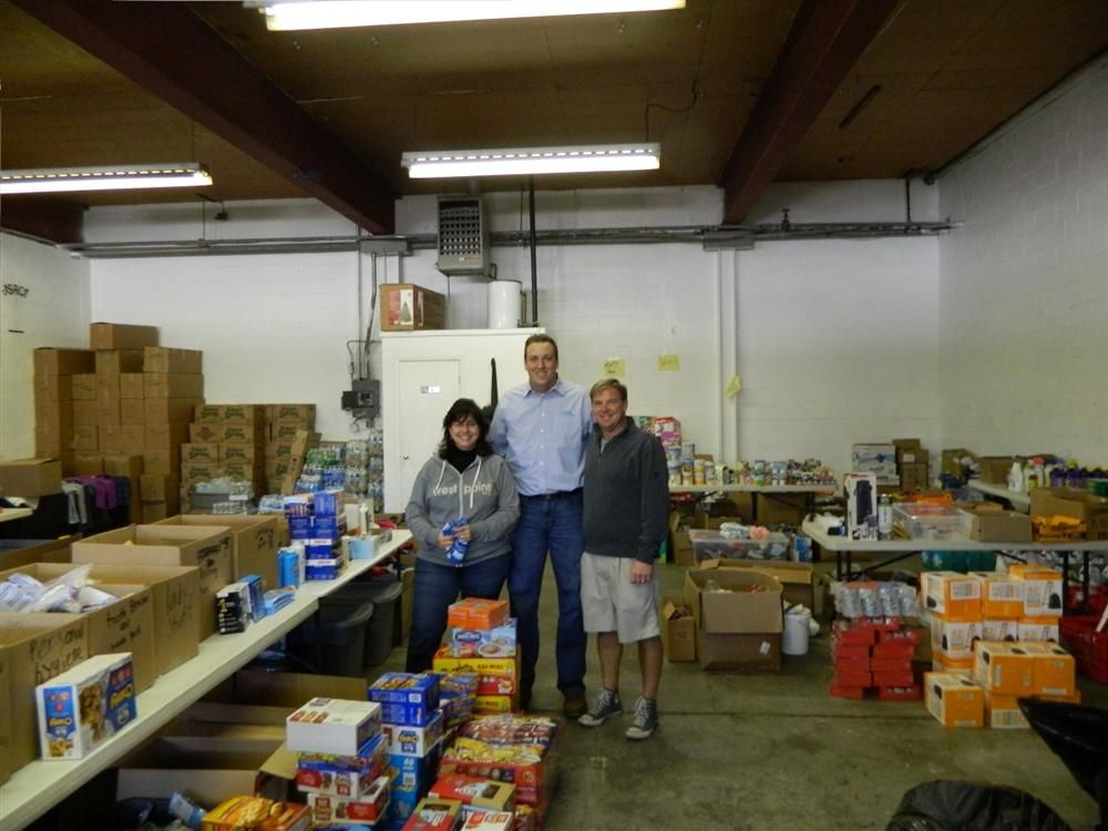 Mark Michael (C), Xylem outside sales representative, poses with two of the volunteers at a shelter.
