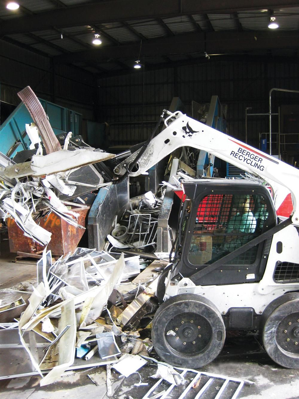 The newest Bobcat loader — an M-Series S750 — easily handles scrap metal with a Bobcat industrial grapple and bucket.