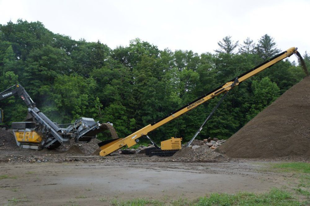 Crushing river rock in Woodstock, Vt., for D&D Excavating, Hartland, Vt. The machines being used are an RM100 2.0 with OS100 screener crushing into an Anaconda TR6036 tracked stacking conveyor. The rock was generated from the Hurricane Irene floods.