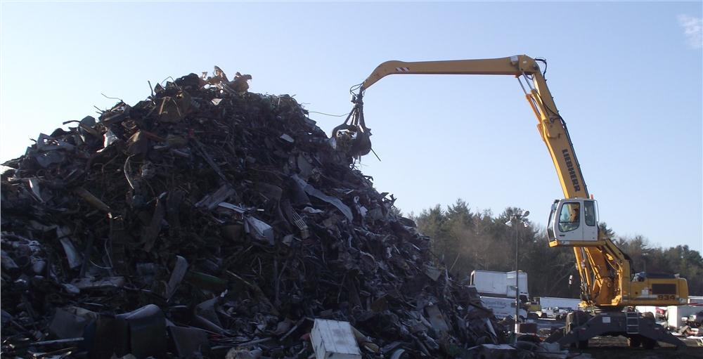The A934C HD Liebherr material handler makes easy use of its grapple to stockpile and load out scrap metal.