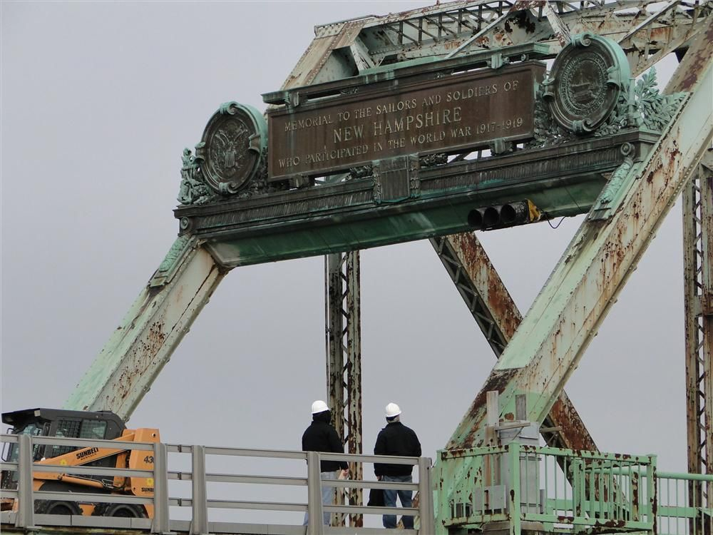 Photo courtesy of Dennis McIntire, Rye, N.H. Workers viewing the plaques and portal monument (undergoing restoration) located on the Portsmouth, N.H., side of the bridge, the dedication markers of the bridge as a WWI Memorial.
