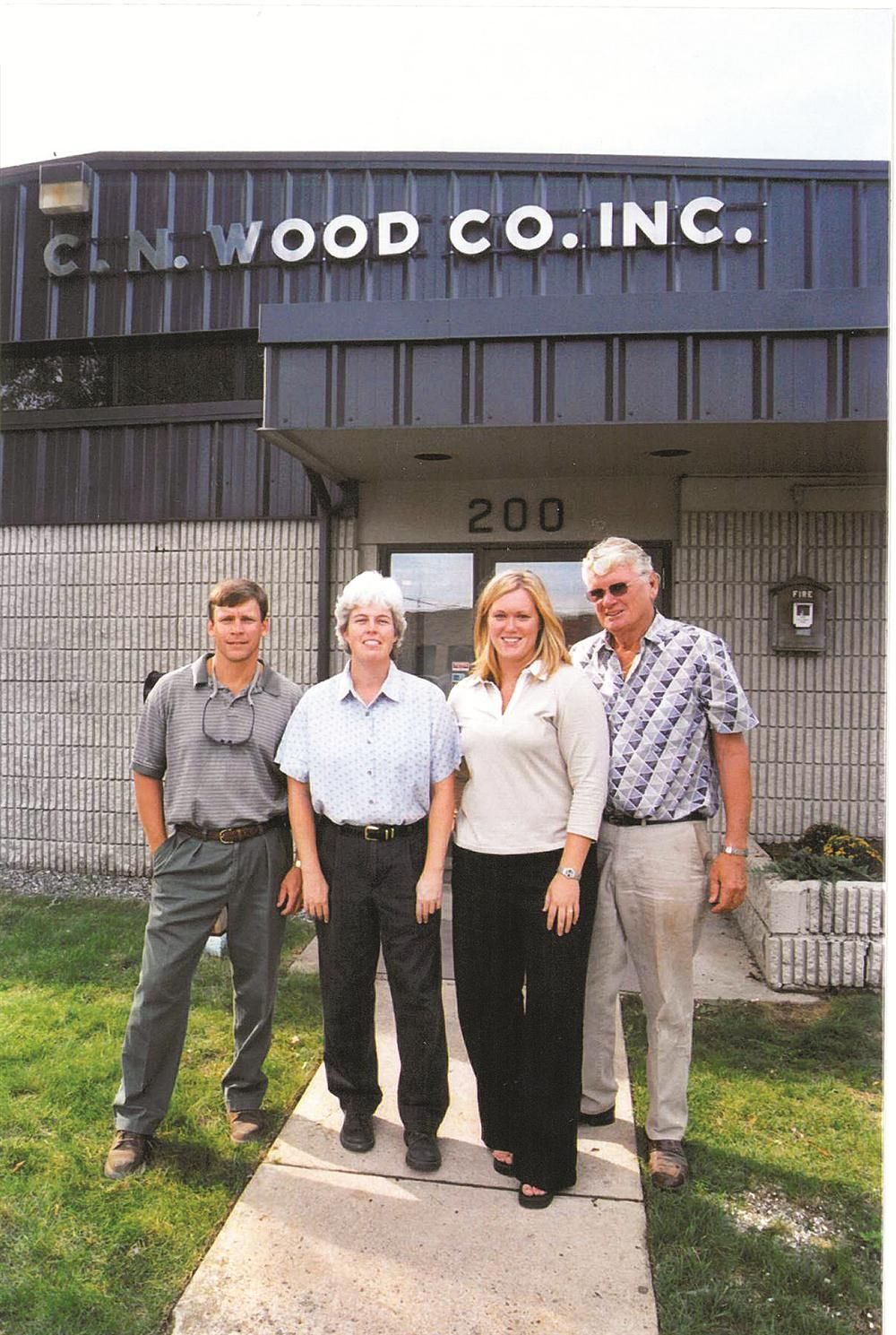 Standing in front of the entrance to C.N. Wood's Woburn facility in 2002. (L-R) are now-CEO Dana MacIver; President Paula Benard; Administrator Paula Piper; and Chairman of the Board Bob Benard.