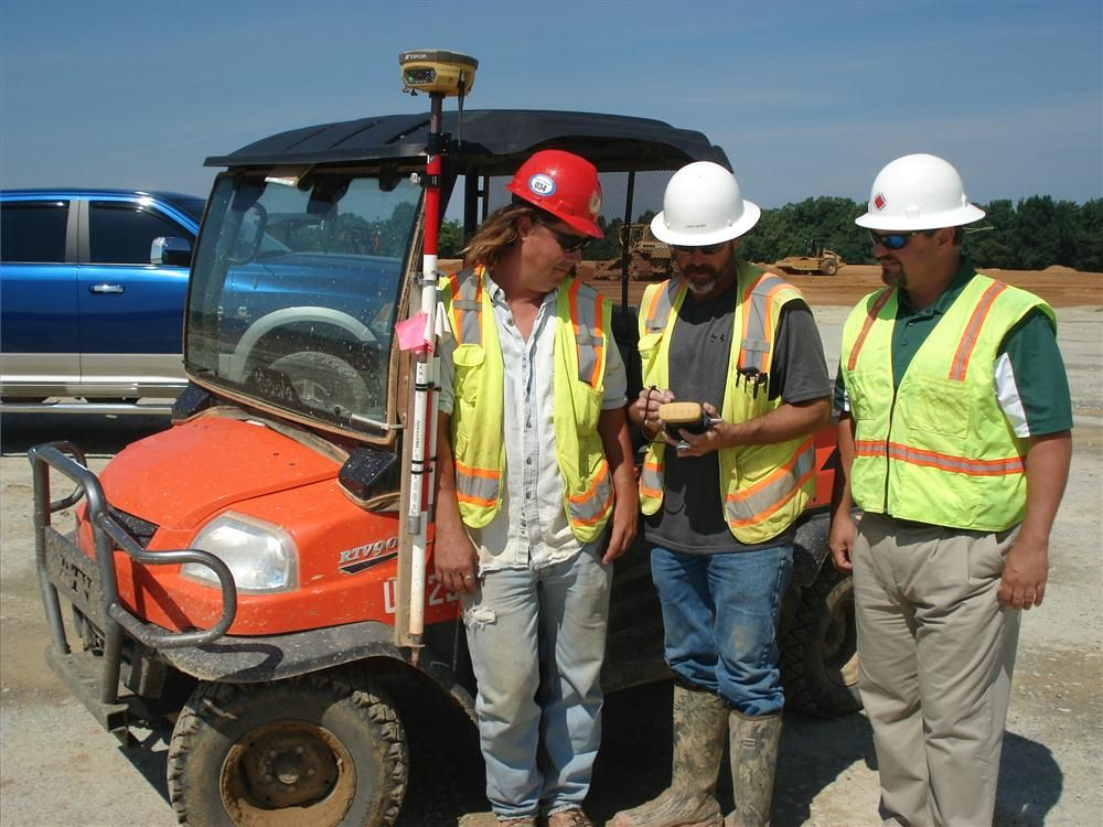 (L-R):?Eddie Miller and John Thompson, both of Glover Construction Company, and Chuck Harris of Benchmark Tool & Supply go over the data supplied by the Topcon hand held FC-500.