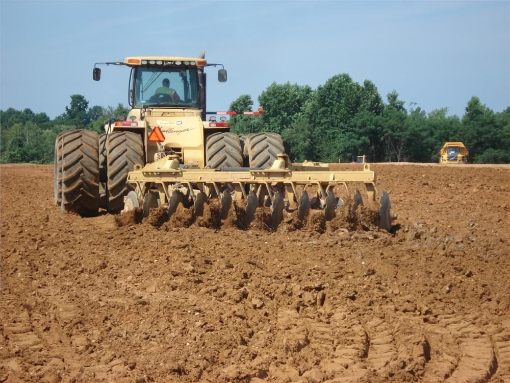 The operator of this Cat Challenger tractor pulls the disk wheels through the soil, breaking it up and allowing it to dry out.
