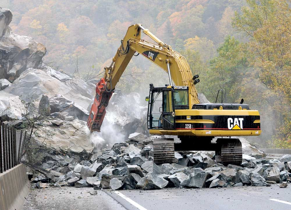 Work begins on clearing a rock slide Oct. 27, 2009, on Interstate 40 in Haywood County, west of Asheville, N.C. Engineers plan to remove as much of the rock at the base of the slide as possible to all
