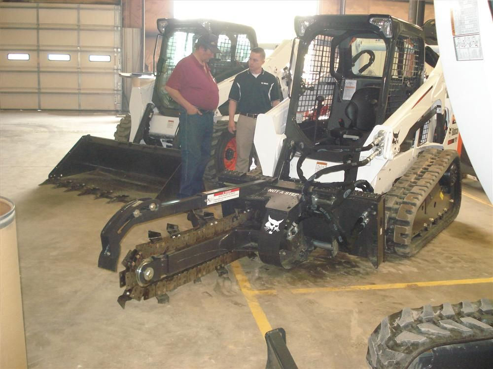 Robert Byars (L) of Byars Heavy Equipment in Spartanburg listens to Freddie Blanton of Bobcat in Spartanburg explain the production capabilities of Bobcat machines and the available attachments.