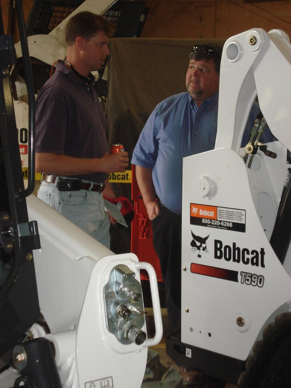 Barry Hedbloom (L) of Hedbloom Builders in Spartanburg looks at different pieces of Bobcat equipment as Steve Payne of Bobcat in Spartanburg explains the recent enhancements of each machine.