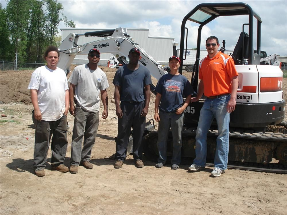 (L-R): Quintin Byrd, Darren Gibson, Davinton Norman and Dory Davis, all of Work Inc. in Spartanburg, wait to test the Bobcat E45 excavator.  Todd Owens of Bobcat of Greenville watches the Bobcat E45 excavator demonstration area.