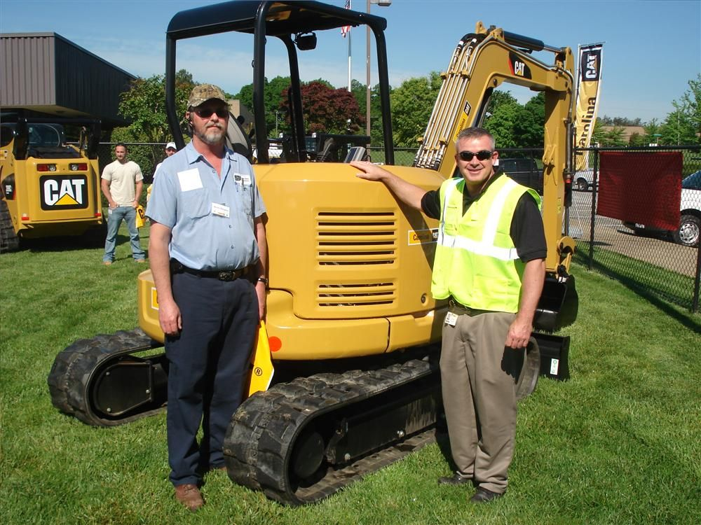 Wade Burgess (L) of State Utility Contractors in Monroe, N.C., and Tony Pennington of Carolina CAT in front of the Cat 305E CR.
