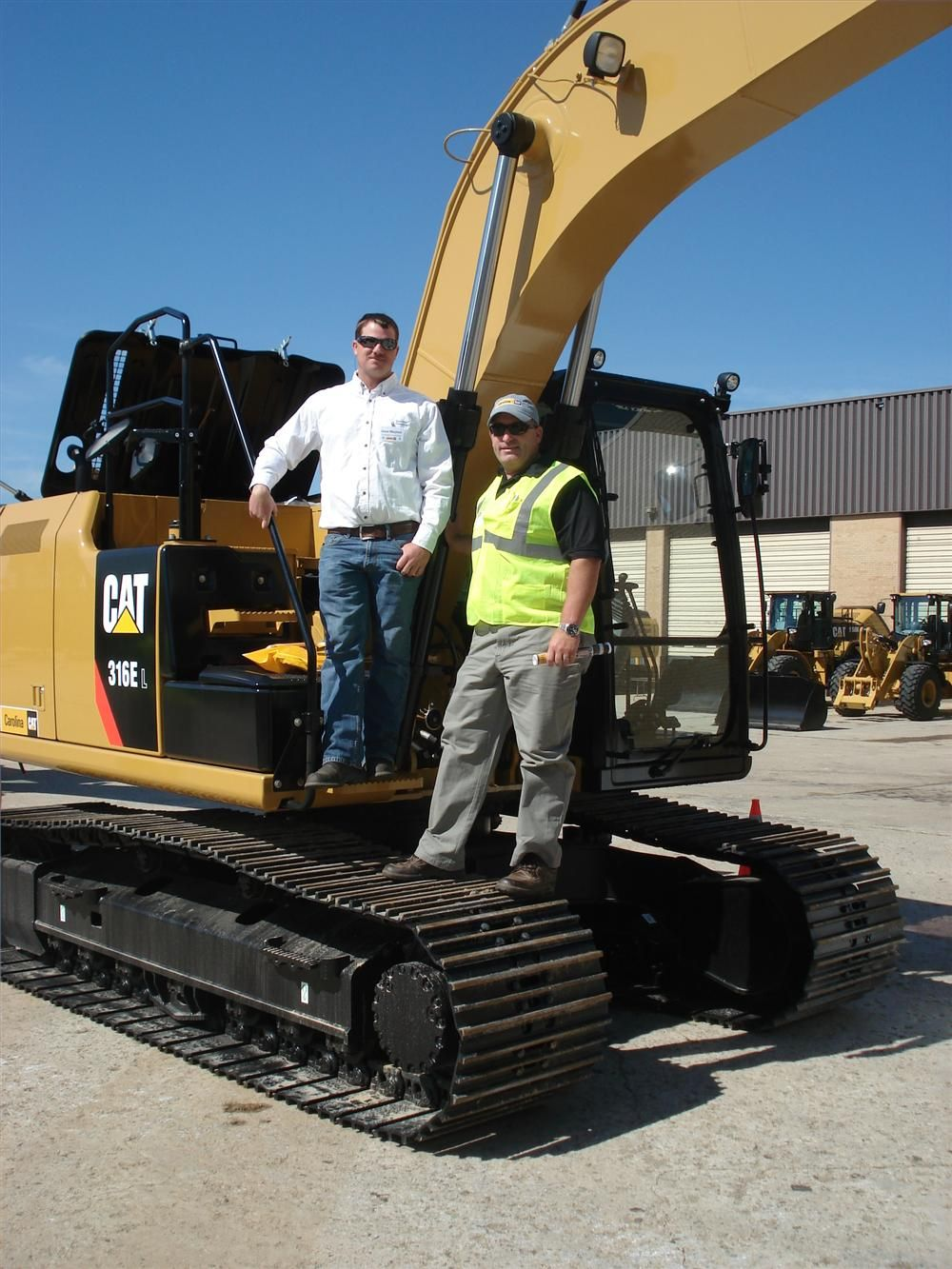 Jason Mayhew (L) of Southland Excavating in Statesville, N.C., looks over the Cat 316E excavator with Brian Hoffman of Carolina CAT.