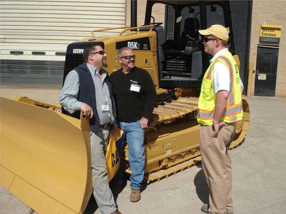 (L-R): Tripp Reed and Jay Garrigan both of C3 Builders in Mt. Ulla, N.C., and Scott Britton of Carolina CAT talk about the Cat D5K track-type tractor.