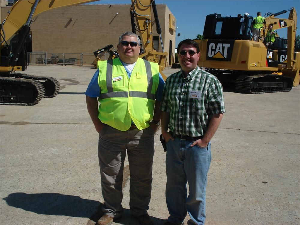 Bryan Henderson (L) of Carolina CAT and Jacob Pinnix of Smith-Rowe LLC in Mt Airy, N.C., go over the full excavator line up.