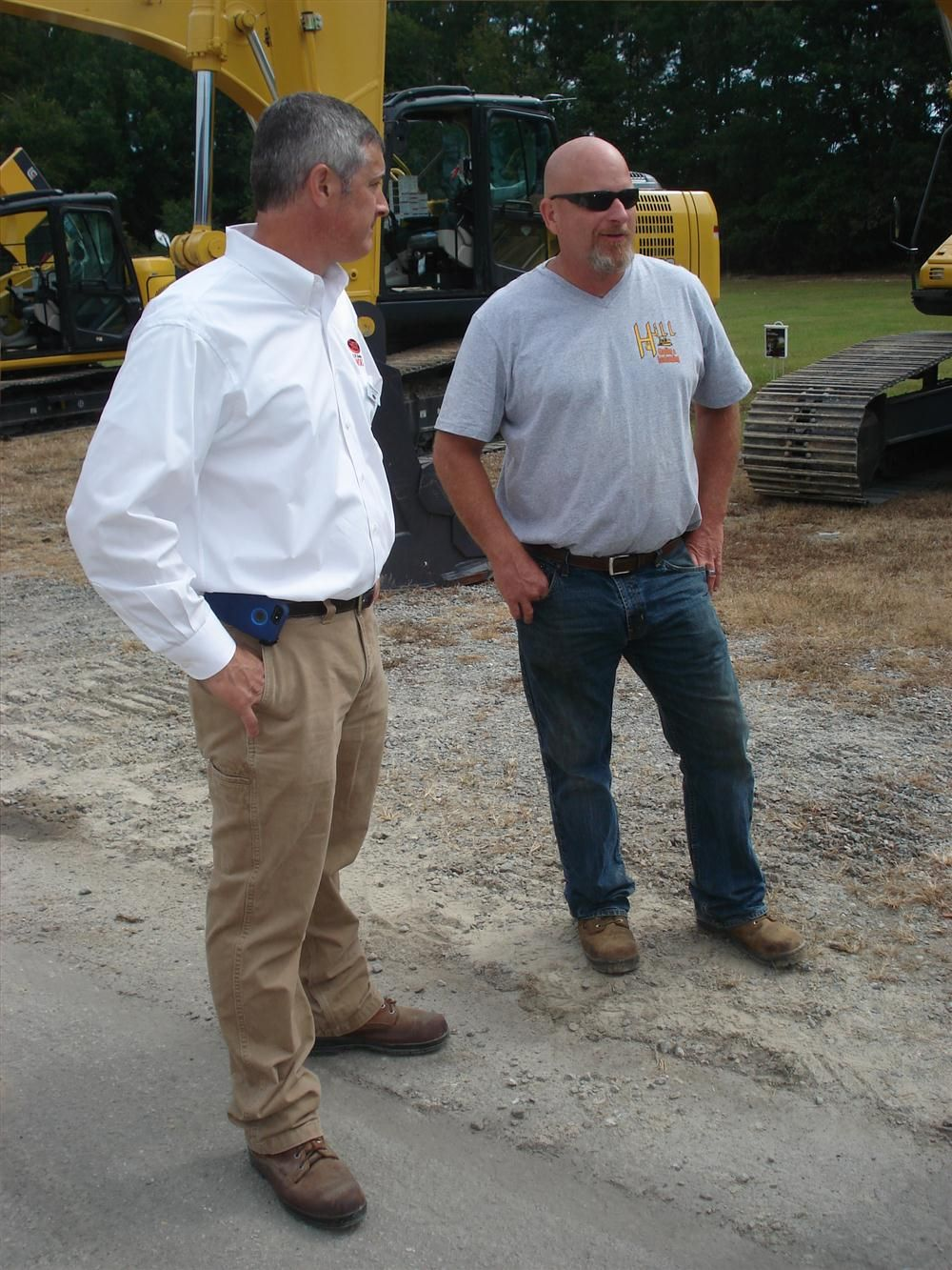 Tom MacGibbon (L) of Company Wrench talks about the Kobelco product line with Eric Hill of Hill Grading & Landscaping in Youngsville, N.C.