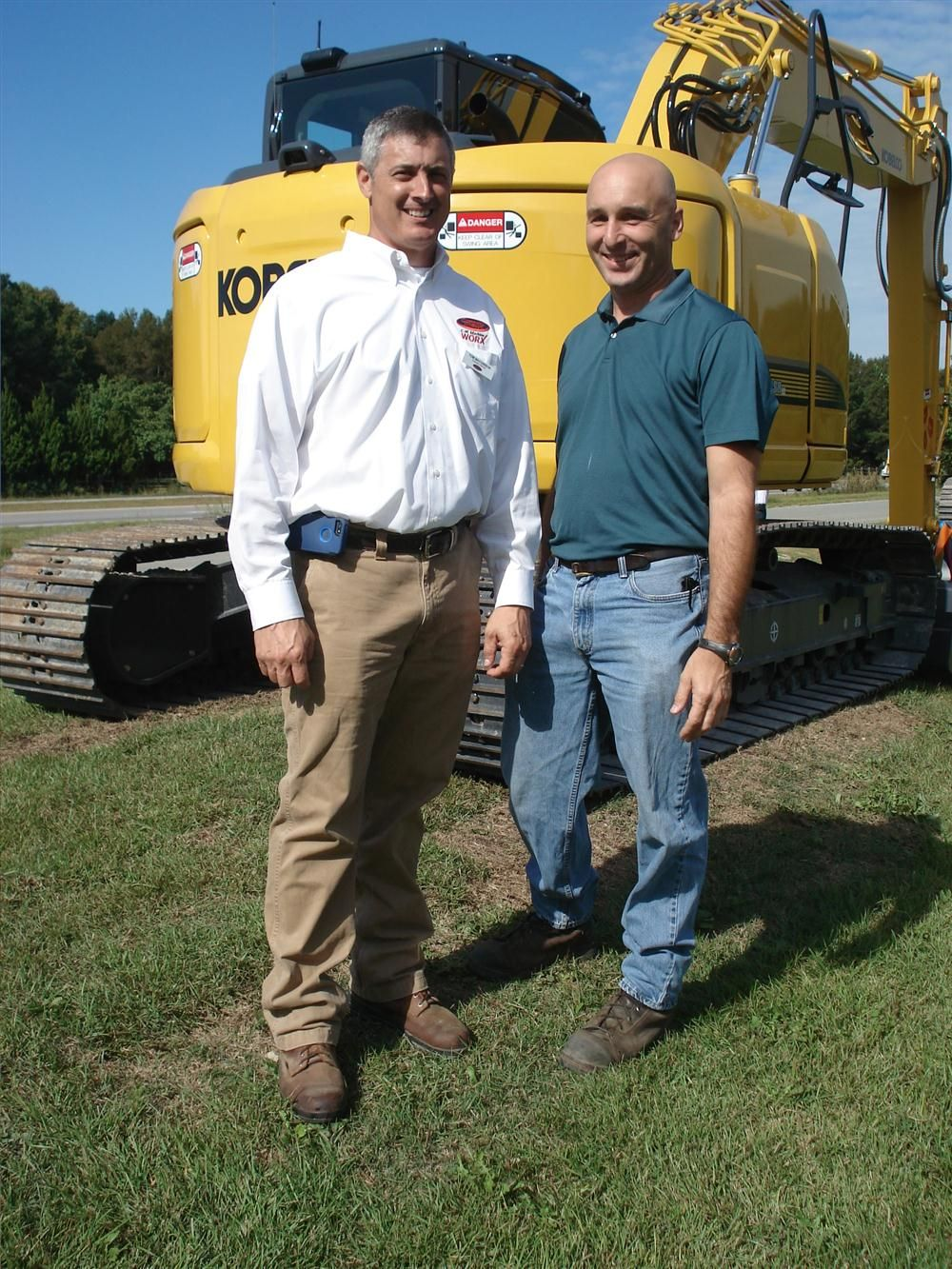 Tom MacGibbon (L) of Company Wrench goes over the Kobelco excavators with Tim Via of Wise Recycling in Clayton, N.C.
