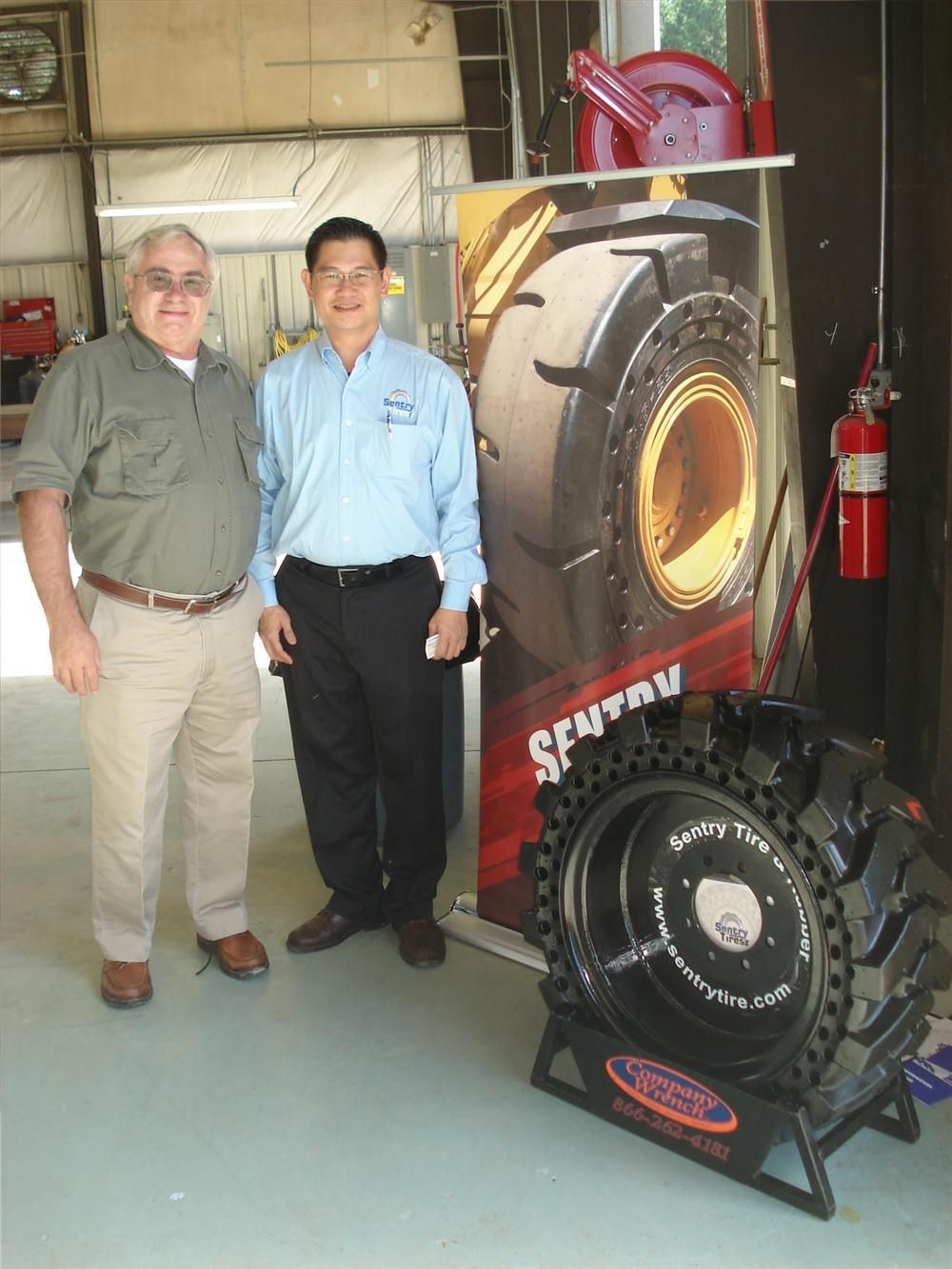 Ken Emmett (L) of Terex talks with Daven Tan of Sentry Tires about the performance and reliability of his products.