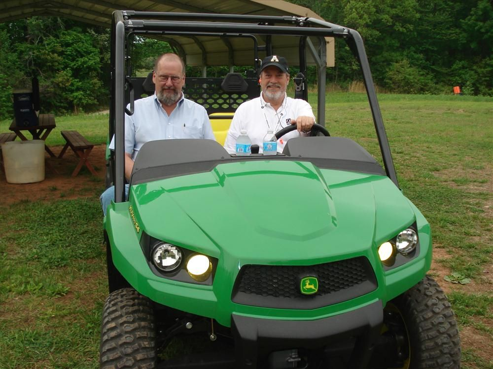 Brad Ratledge (L) of Vulcan Materials East region and Marcus Archer of James River Equipment drive around the course.