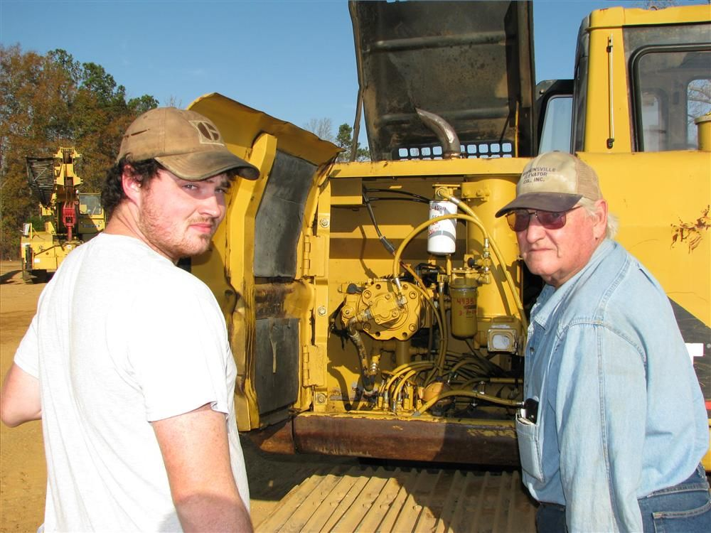 Opening up a Cat 312BL for inspection and consideration for use in their farming operation are Carroll McPherson (L) and Carroll Browning, Browning Farms, Auburn, Ky.
