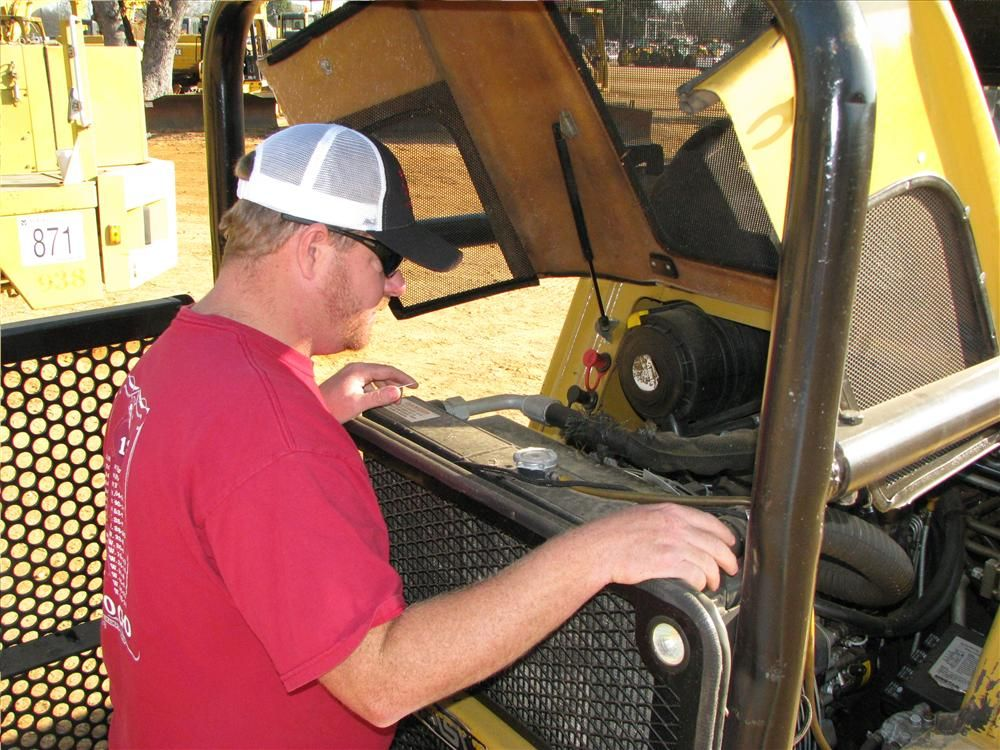 Jimmy Lawler, Lawler Timber Company, Camden, Ala., examines an ASV Positrack RC100 with mulcher attachment and forestry package.