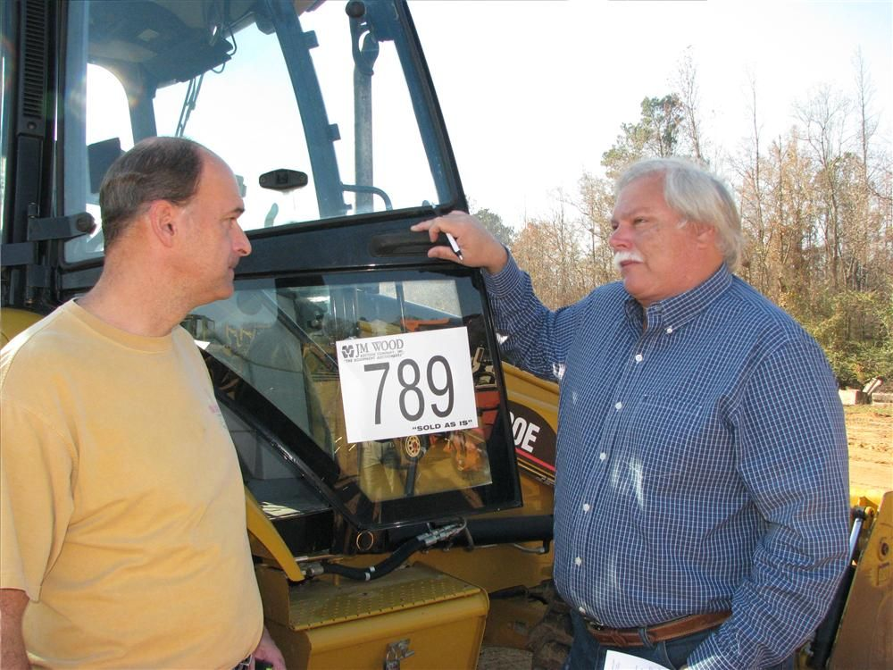 Deep in conversation about the Cat 420E backhoe loader are Jeff Harbin (L), PT Harbin Farms, The Shoals, Ala., and Greg Reed, Reed Construction, Jasper, Ala.