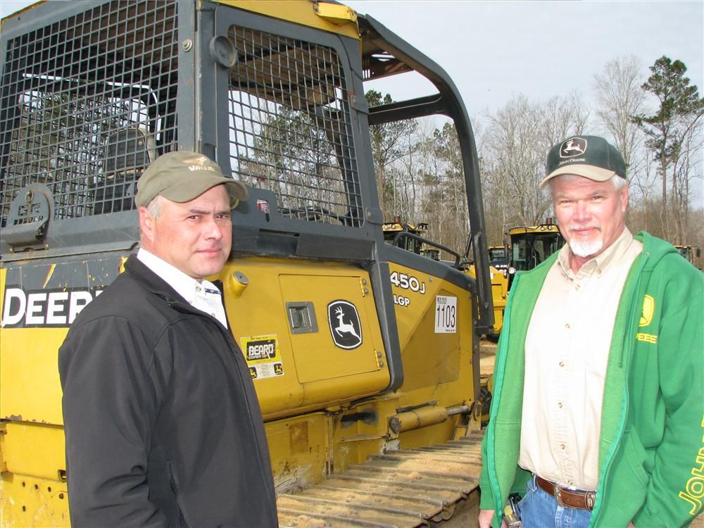 Jody McMinn (L) of Jake McMinn Farms, Potts Camp, Miss., and Paul Fowler of Fowler Tile & Excavating, Northport, Ala., are looking over some of the smaller dozers in the sale lineup, including this John Deere 450J LGP.