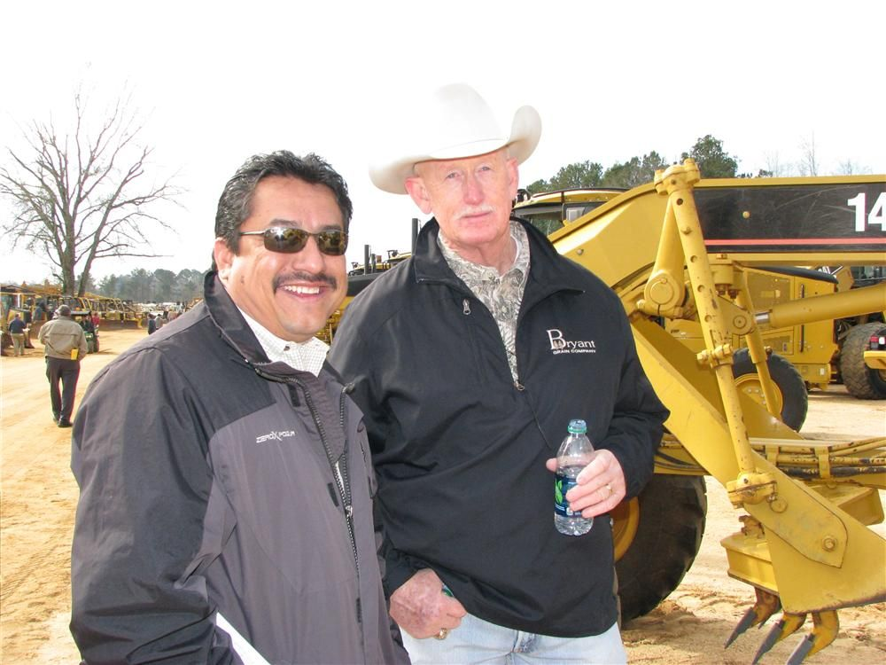 Jesus Ramirez (L) of Gibbs and Sons Machinery, Gadsden, Ala., and Charlie Calhoun of Calhoun Tractor Co., Aledo, Texas, try their best to estimate where the pricing will go on some of the machines in the sale lineup.