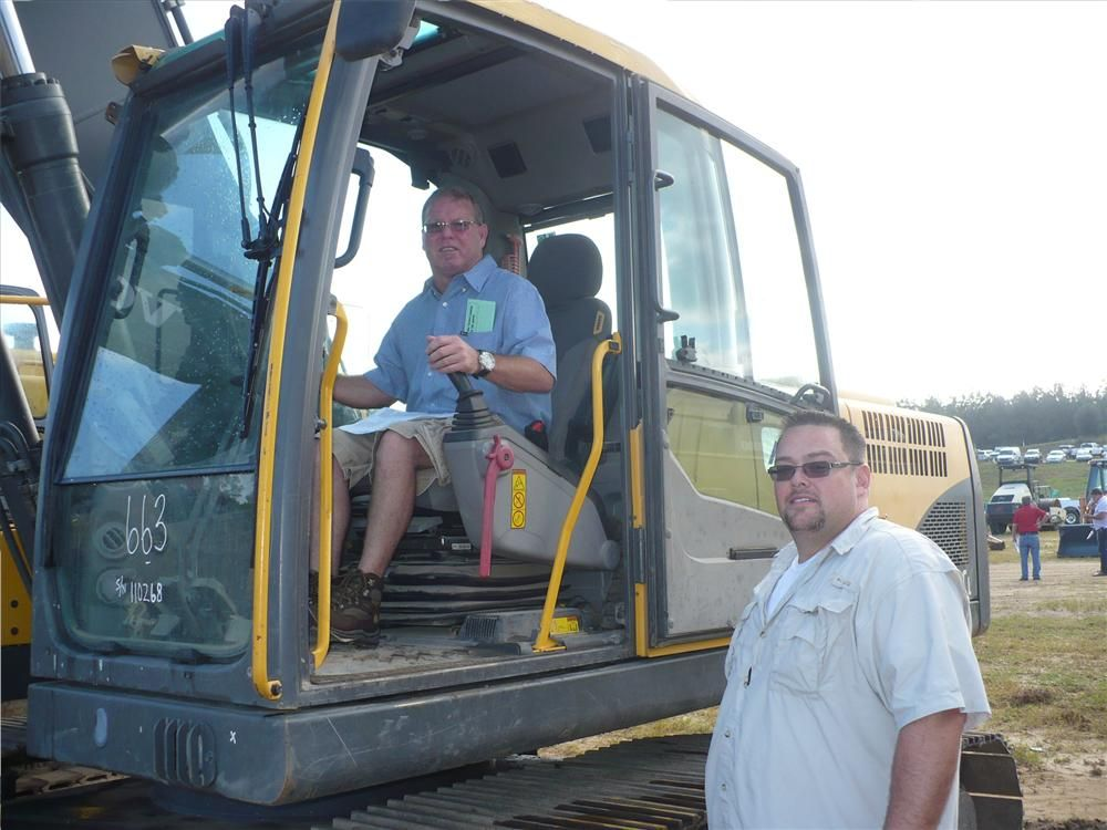 Chris Johnson (L), used equipment manager, Alta Equipment Co., New Hudson, Mich., tries out this Volvo EC 240Cl as Ryan Sebero, president, SJ Equipment, Macomb, Mich., looks on.