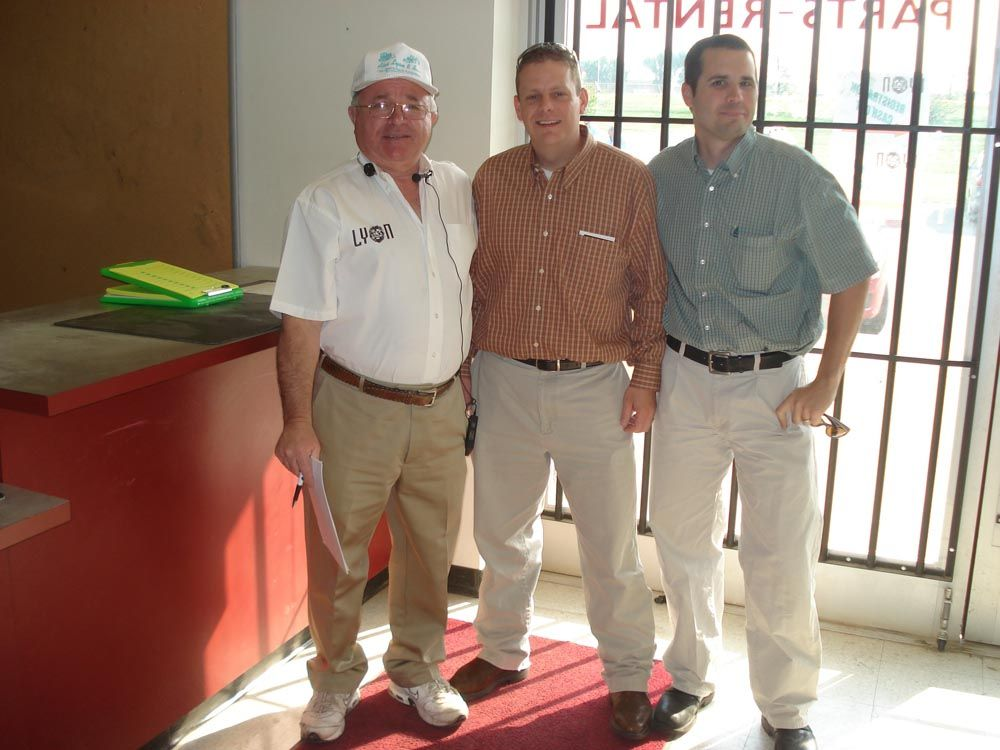 (L-R): Jack Lyon welcomes James Dennis and Brad Coverdale, both with Sunbelt Rentals, to the auction.