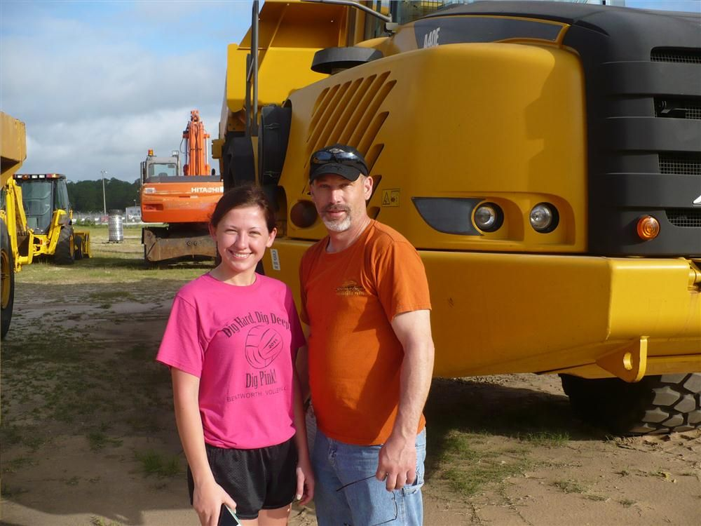 Karli and Paul Kubincanek of 18 Karat Inc. enjoy some father and daughter time and consider this Volvo A40E truck.