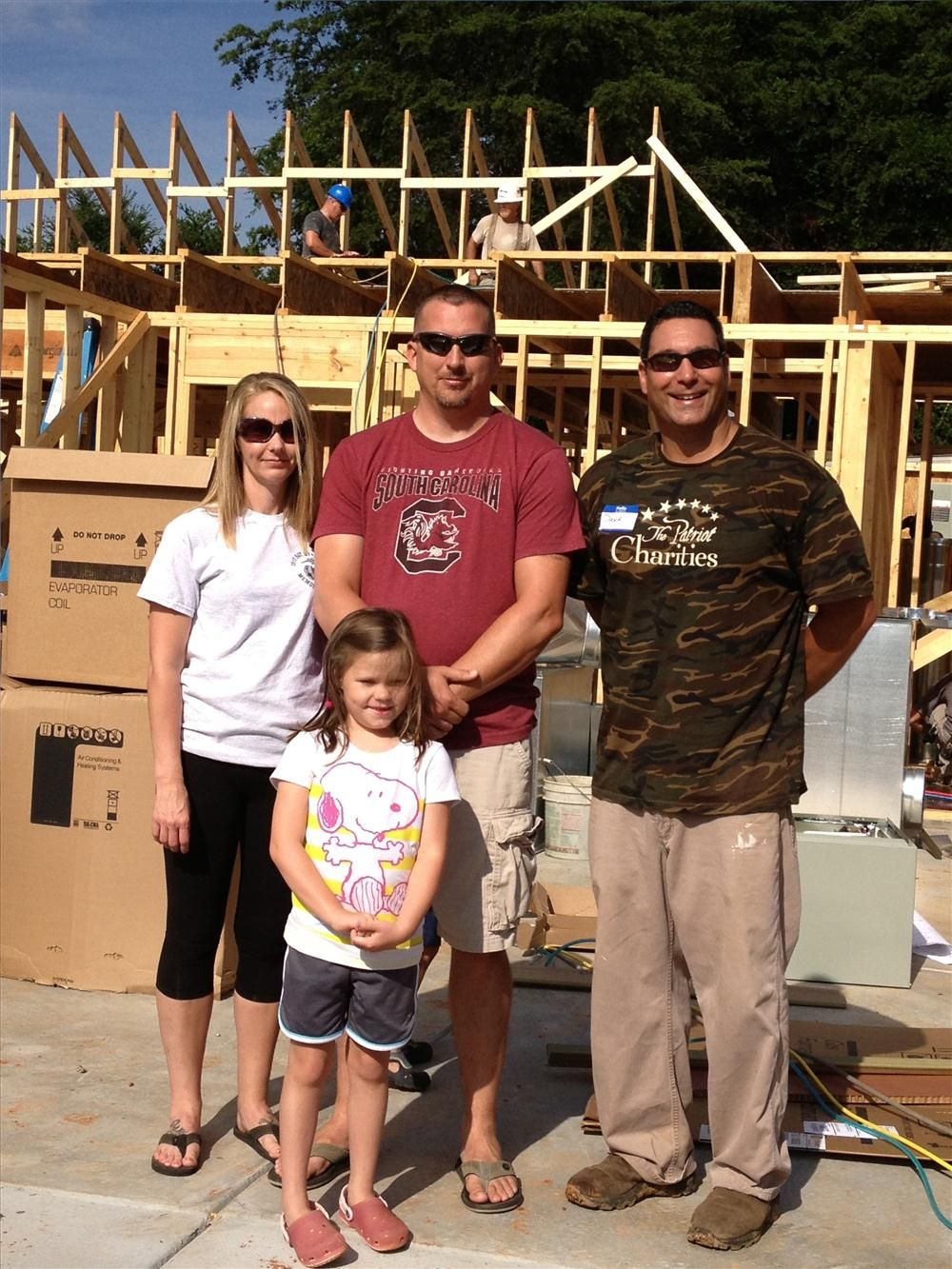 (L-R): Michele Hyde, Emily Hyde, Sgt. Jason Hyde and Dana Bradley, president of The Patriot Charities stand in front of the Hyde's future home.