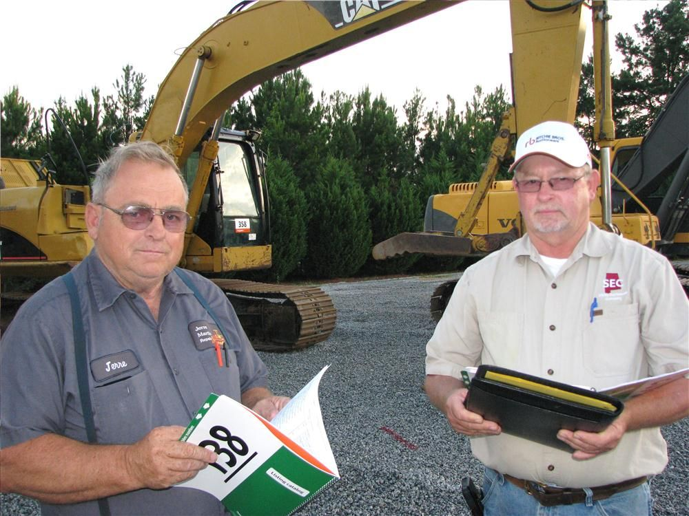 Jerre Martin (L), Jerre Martin Repair, Ephrata, Pa., and Billy Sibley of Sibley Equipment Company, Woodstock, Ala., look over their notes on the lineup of excavators.