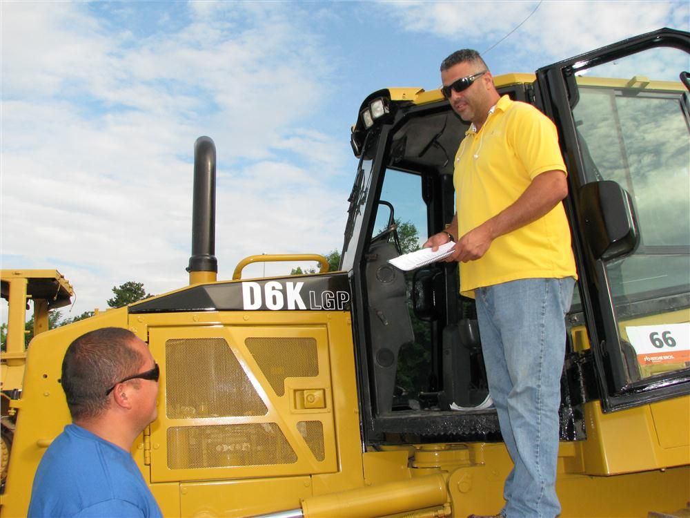 Carlos Rivera (L) and Orlando Zenon, both of Zenon & Zenon Contractors, Stockbridge, Ga., inspect this Cat D6K LGP.