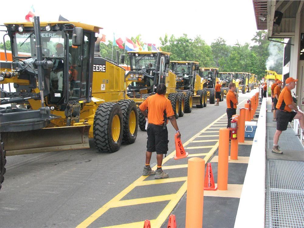 "A package of 2011 Deere 772GP motorgraders rolls onto the ramp as ""choice of nine machines."""