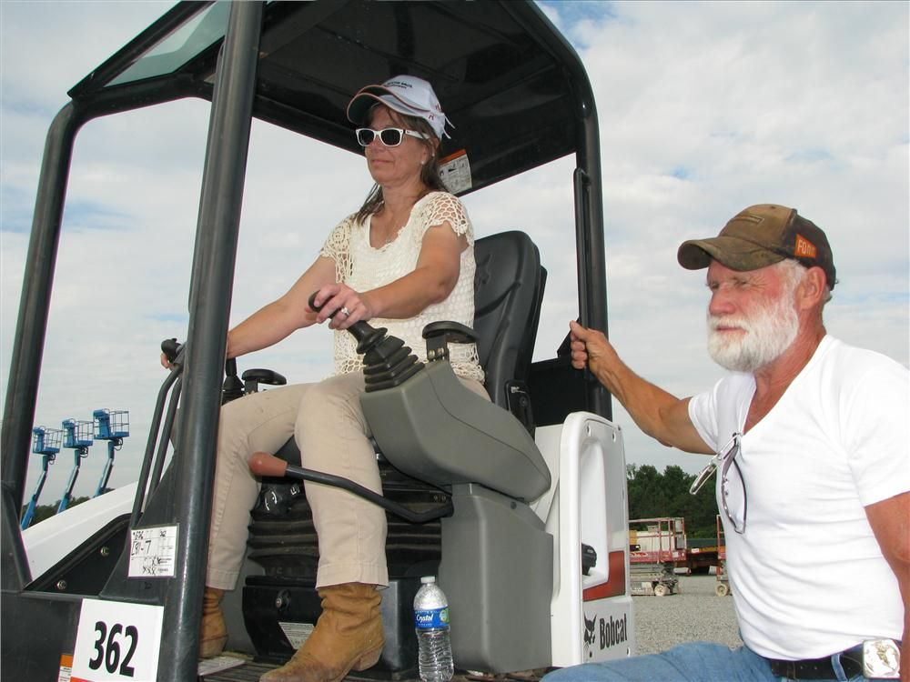 Dawn Ewing and Roy Ewing of W & S Maintenance Unlimited Inc., Asheville, N.C., test out this Bobcat E32.