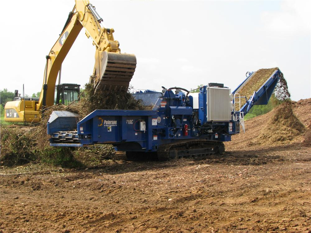A Thompson Tractor equipment operator uses a Caterpillar 329DL excavator to load up a Peterson 5710C horizontal grinder to show how quickly a 1,050 hp. (782 kW) Cat-powered Peterson machine can grind wood waste into mulch.