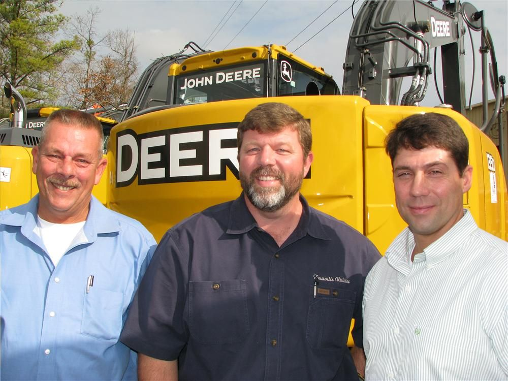 Taking a look at the new model machines including a Deere 135D excavator are (L-R) Harold Chamblee and Alan Long of Trussville Utilities, Trussville, Ala.; with their Warrior Tractor sales representative, Mike Sims.
