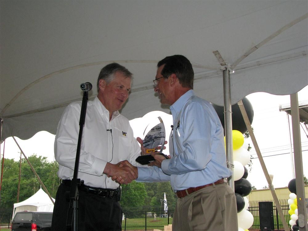 As the speeches concluded, Doug Oberhelman (L), CEO of Caterpillar, presents the 100th anniversary commemorative award to Jim Stephenson, chairman and CEO of Yancey Bros. Co.