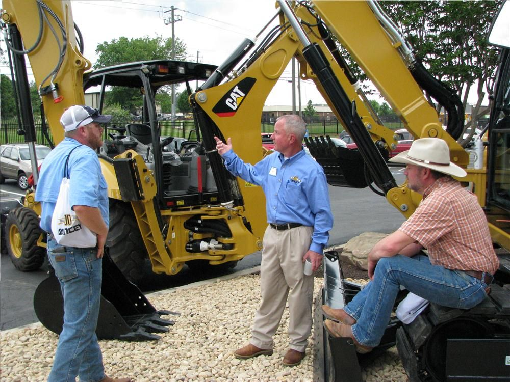 Darren Story (C) goes over the features of the Cat 308E excavator with Cameron Kerr (L) and Dean Holt  of Southern Resource Management, Newnan, Ga.