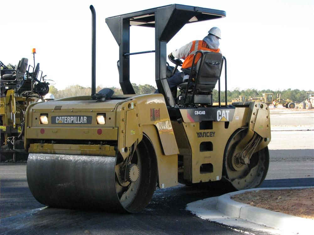 An Allied Paving operator does some tight rolling at the curbing with a Cat CB434D dual drum compactor.