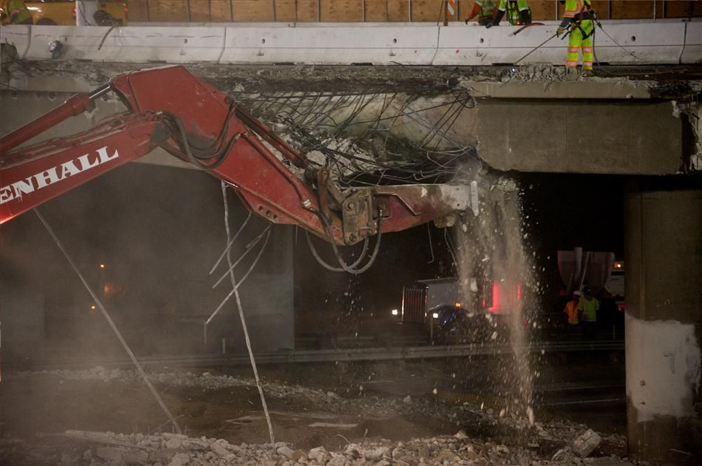 In the early morning hours, a Pennhall hoe-ram demolishes the Skirball Center Drive Bridge. Soil was spread beneath the bridge to protect the roadway from falling concrete.
