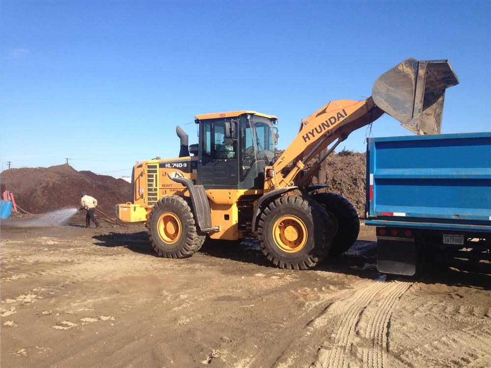 The HL740-9 loading trucks with mulch to be hauled to wood burning facilities.