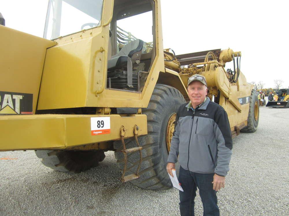 Carl Hoerr, president of Hoerr Machinery LLC, looks over this Cat 615C scraper.