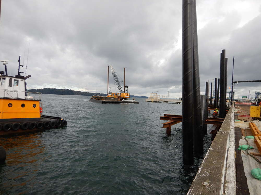 Quigg Bros. has several barges on site at any given time, whether as a laydown area or for impact pile driving. On the farthest barge, its crew is working on impact pile driving in preparation for seismic bracing.