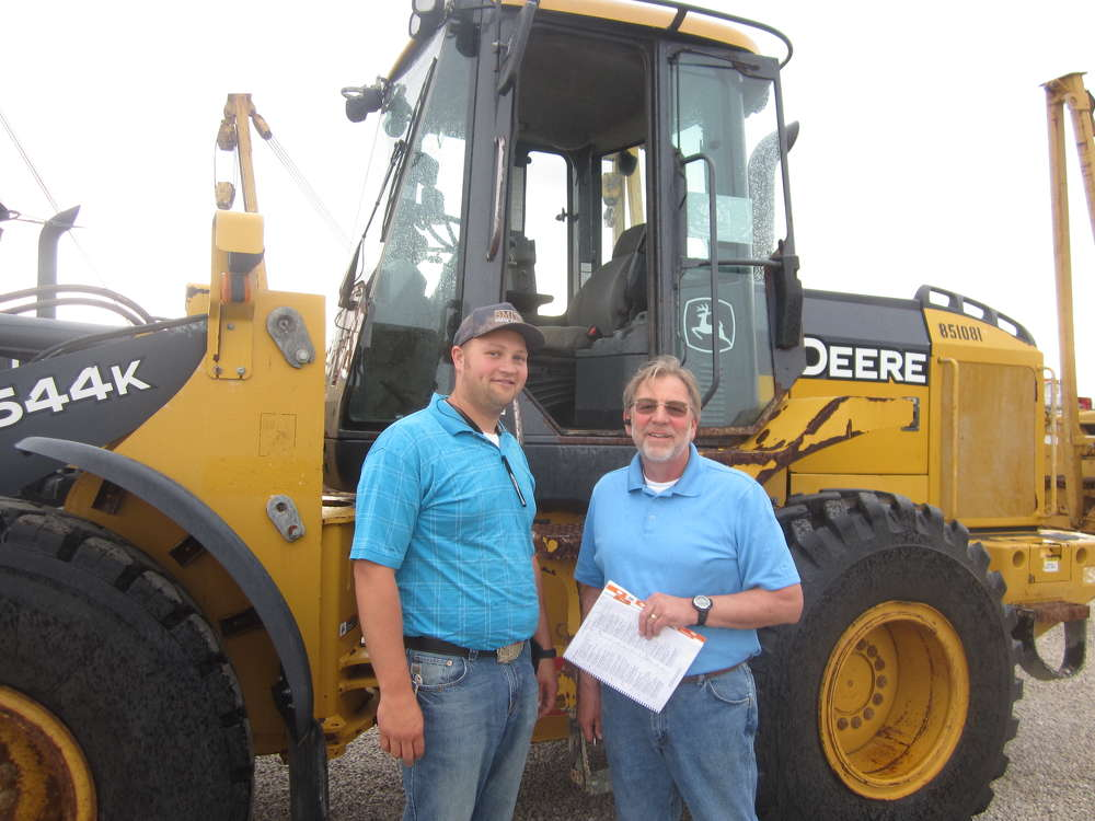 Colton and Brad Smith, both of R&R Construction, shop for a deal on a wheel loader.