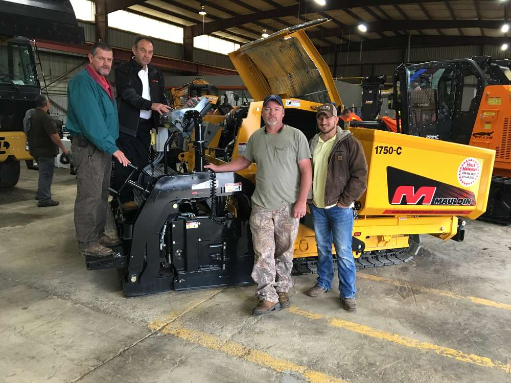 Larry Martin (L) of Calder Brothers, Manufacturers of Mauldin Paving Products, stands at the controls of the company's very popular Mauldin 1750C.  (L-R) are Tony Pritchard, Johnny Gardner and Sam Lawhorn all of Blythe Brothers Asphalt in Charlotte.