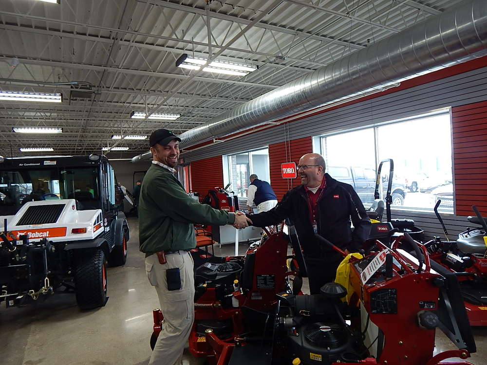 During the Burnsville open house, Ben Boeding (L), park mainteneance supervisor of the city of Eagan, Minn., stands with Jon Almquist, Toro district sales manager, Bloomington, Minn., and the new Toro Grand Stand mower series.