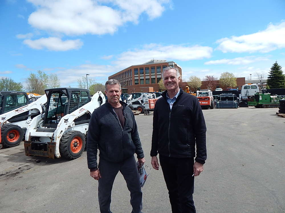 Ron Smith (L) of Farmington, Minn., catches up with Bill Quirk, Tri-State Bobcat owner, at the Burnsville open house.