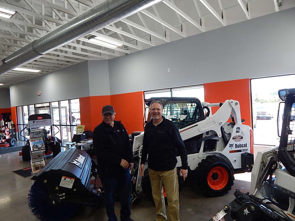Jeff Varner (L), Tri-State Bobcat salesman, stands with Milo Johnson, Bobcat regional director of dealer accounts Midwest, near a new Bobcat S595 in the huge indoor showroom in Tri-State Bobcat's Hudson location.