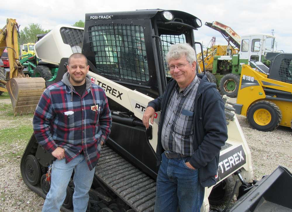 Andy Billheimer (L) of Battle Zone Paintball Park in Mansfield, talks about this Terex PT-80 skid steer loader with Dan Hayes of Dan's Tree Enterprises.