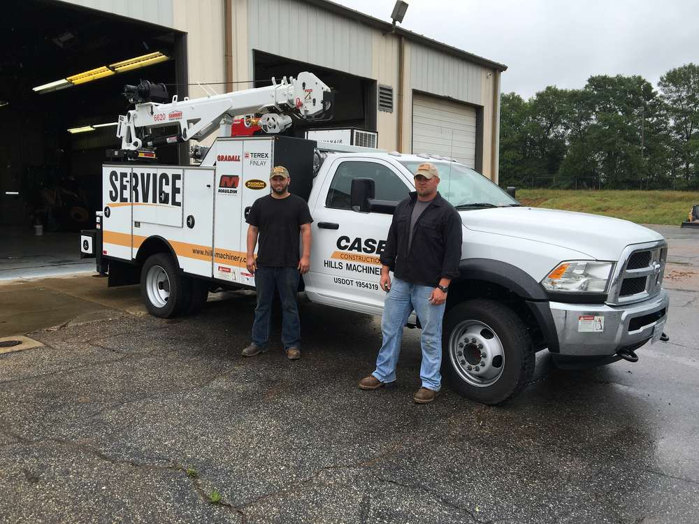 Chris Head (L) and Jarrett Kitchen stand in front of one of the two fully equipped service trucks based in Greenville.