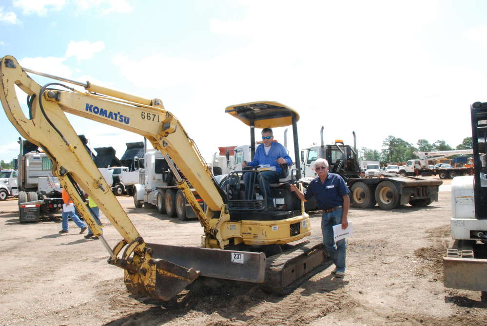 Ronnie (L) and Donnie Foley, both of Mobil Equipment III LLC out of Robertsdale, Ala., stop to look at one of the many mini-excavators consigned to the Brooklyn, Miss., auction.